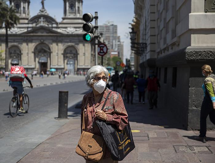 Persona mayor con mascarilla detenida en la calle y de fondo se ve la Catedral Metropolitana