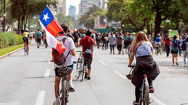Personas en bicicleta con bandera chilena